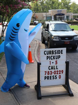 Tiffany DeVries, Miller Branch Library manager delivers books to curbside pickup wearing a shark suit, Friday, Aug. 21, 2020, at the Main Library. Library Director Jennifer Goodson said that the library staff wanted to share a smile during the day with library patrons. The Main Library is now open for brief visits, Monday through Friday, 9 a.m. to 5:30 p.m.  Appointments are required, and not all library resources are available.