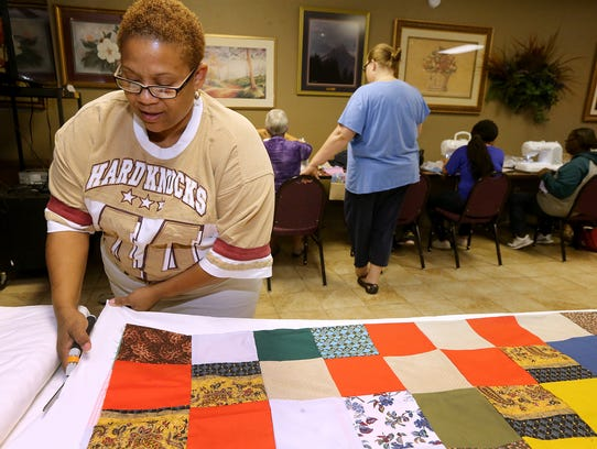 Charlene Triche cuts the backing for her quilt during