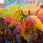 Runners throw color powder packets during a post race celebration at the Tempe Beach Park. The Color Run is a 5K run where runners are doused in color power at every mile.