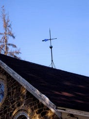 A simple weather vane with a lightning rod on a stone