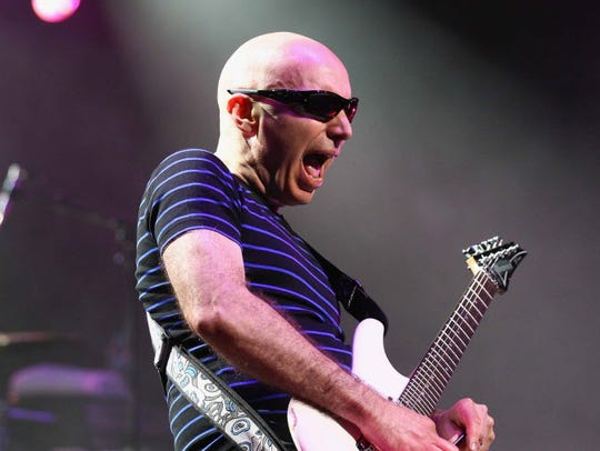 Joe Satriani performs with Def Leppard's Phil Collen