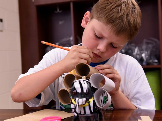 Kolby Darr adds boosters to his robotic dog during Camp Invention in 2018 at Coshocton Elementary School.