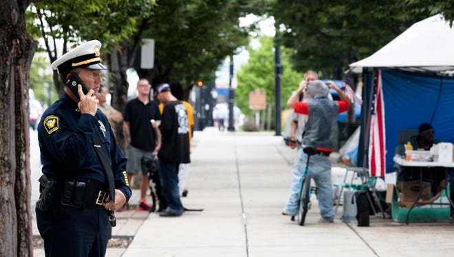 Cincinnati Police Captain Michael Neville speaks on the phone while assisting to inform homeless on Tuesday, July 31, 2018 in downtown Cincinnati that they have 72 hours to vacate 3rd Street.