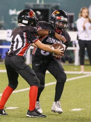 The Hanover Tigers played the Parsippany PAL Red Hawks at halftime of the Jets-Falcons preseason game at MetLife Stadium on August 21, 2015. Red Hawks' Campbell Pivnick, #10, left, hands off to Xavion Crosby,  #34.