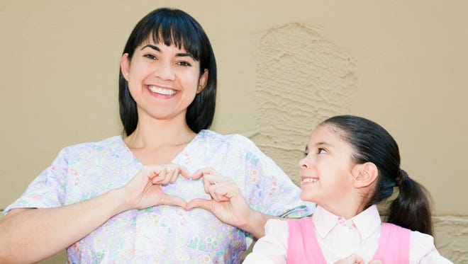 Nurse and girl making heart shaped gesture