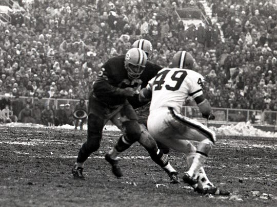 Green Bay Packers halfback Paul Hornung (5) heads upfield as guard Fuzzy Thurston (63) blocks Cleveland Browns cornerback Walter Beach (49) during the NFL championship game at Lambeau Field on Jan. 2, 1966. The Packers won 23-12. Press-Gazette archives