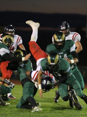 Regis defenders take down Kennedy's Bishop Mitchell as the Rams defeat the Trojans 15-7 in a Tri-River Conference game on Friday, Sept. 30, 2016, in Stayton.
