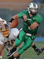 Badin senior QB Patrick Coyne, a UC commit, evades tacklers as he is flushed out of the pocket during the game against Ross, Friday, September 11th, 2009.