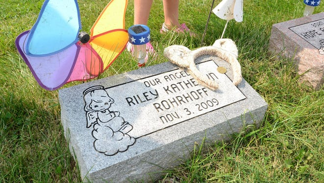 Payton Rohrhoff, 5, stands next to the grave of her twin sister Riley at the South Lyon Cemetery.