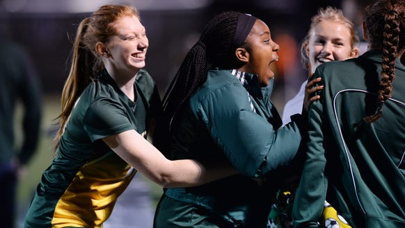 Reynolds soccer players celebrate a goal on the sidelines