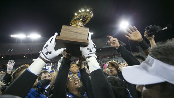 Chandler players celebrate with the championship trophy after their 49-42 win over Perry during the 6A high school football state championship game at Arizona Stadium in Tucson on Saturday, December 2, 2017.