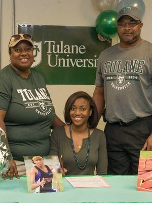 Kyah Loyd signs with Tulane while flanked by her parents.