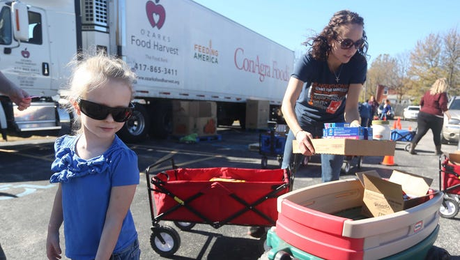 Ozarks Food Harvest distributes food at Reed Middle School from their mobile food pantry. Zoe Gormley, 4, gets a wagon filled with food. Donations to Ozarks Food Harvest on during the 'Transform Hunger Into Hope' food drive fund this program. The Ozarks Food Harvest distributes food at Reed Middle School from their mobile food pantry. Zoe Gormley, 4, gets a wagon filled with food. Donations to Ozarks Food Harvest on Giving Tuesday will help fund this program.