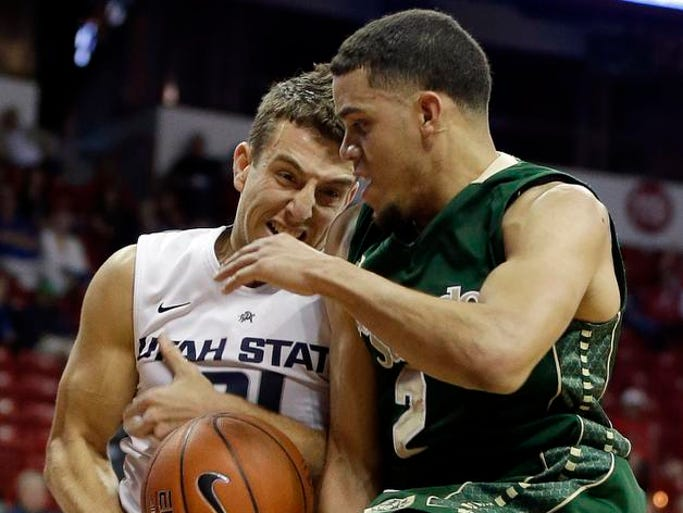 Colorado State's Daniel Bejarano and Utah State's Spencer Butterfield try to pull down a rebound during a Mountain West Conference tournament NCAA college basketball game Wednesday, March 12, 2014, in Las Vegas.
