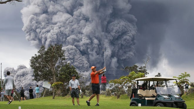 People play golf as an ash plume rises in the distance from the Kilauea volcano on Hawaii's Big Island May 15, 2018 in Hawaii Volcanoes National Park, Hawaii.