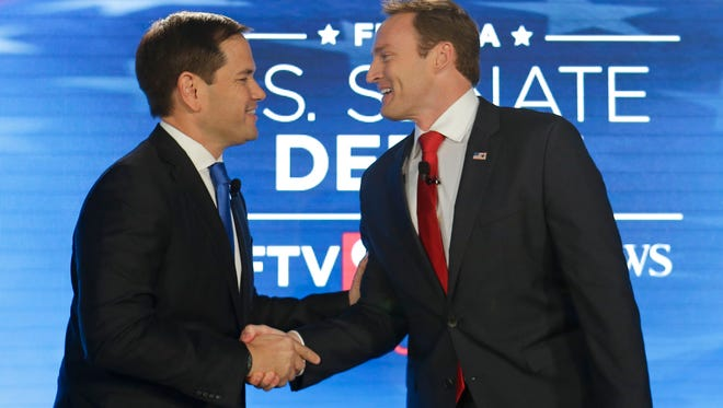 Sen. Marco Rubio, R-Fla., left, and Rep. Patrick Murphy, D-Fla., shake hands before their debate at the University of Central Florida, Monday, Oct. 17, 2016, in Orlando. (AP Photo/John Raoux)