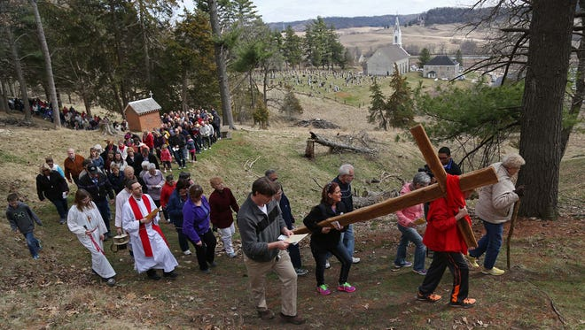 A group of people help carry a large wooden cross through the St. Donatus Catholic Church outdoor Way of the Cross on Good Friday, April 3, 2015. St. Donatus is home to the first outdoor way of the cross in the United States.