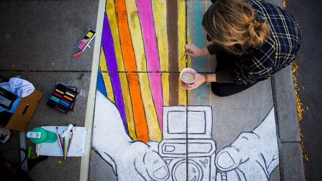 Kelsey Adams draws on the sidewalk outside of Lentz & Company on Ludlow Avenue for CliftonFest Saturday, October 8, 2016.