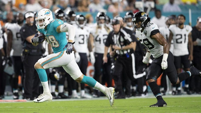 Miami Dolphins tight end Mike Gesicki runs after a catch getting past Jacksonville Jaguars linebacker D.J. Alexander.