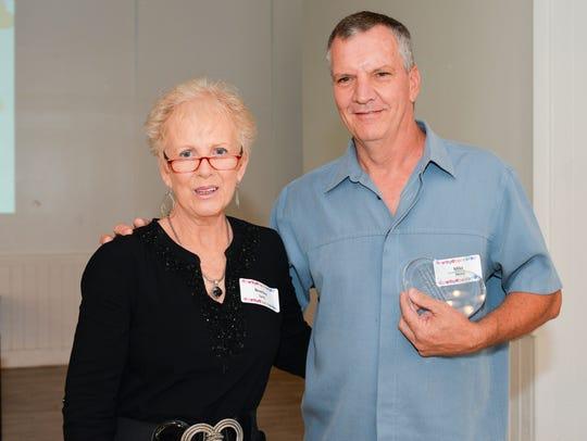 Volunteer Beverley Sarlo, left, presents St. Lucie