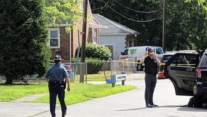 A Massachusetts state trooper walks near the scene on Tuttle Street in Saugus.