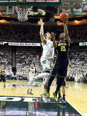 MSU center Matt Costello (10) blocks shot by Michigan's Zak Irvin during the second half of the Spartans' 76-66 overtime win Sunday at Breslin Center. Costello finished with 10 points, seven rebounds and four blocked shots.