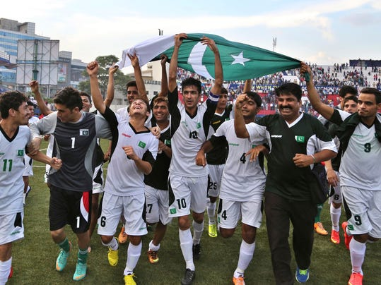 Pakistan team captain Kaleem Ullah, center (10), flanked by fellow team members and support staff take the victory lap as they celebrate their win after the last match of the two-match friendly soccer tournament between Indian and Pakistan in Bangalore, India, Wednesday, Aug. 20, 2014. Pakistan won the match 2-0 to level the series. (AP Photo/Aijaz Rahi)