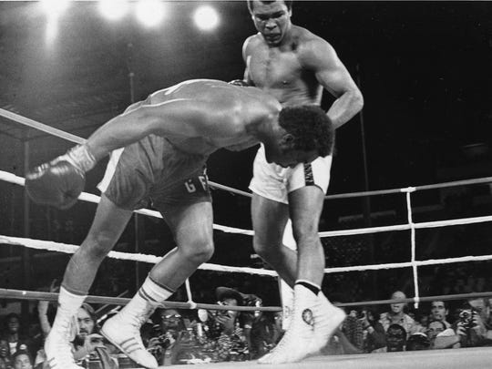 In this Oct. 30, 1974, file photo, challenger Muhammad Ali watches as defending world champion George Foreman goes down to the canvas in the eighth round of their WBA/WBC championship match in Kinshasa, Zaire. Ali, the magnificent heavyweight champion whose fast fists and irrepressible personality transcended sports and captivated the world, died Friday. He was 74.