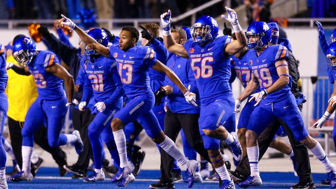 Boise State cornerback Marques Evans (13) and Boise State linebacker Joseph Inda (56) celebrate after the final play against Utah State in an NCAA college football game, Saturday, Nov. 24, 2018, in Boise, Idaho. Boise State won 33-24. (AP Photo/Steve Conner)