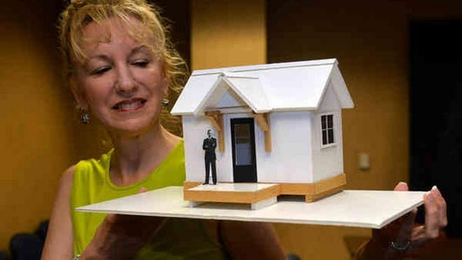 """Cindy Murphy Kelley, executive director of the Chatham Savannah Authority for the Homeless, holds a model of the single-resident """"tiny houses"""" in 2016, homes that are now becoming a reality."""