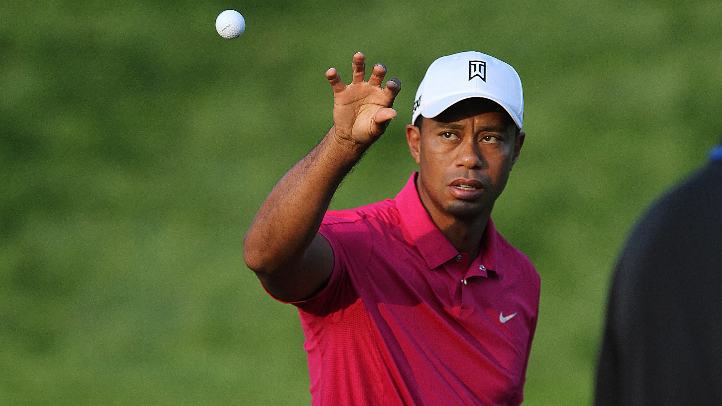 Tiger Woods grabs a ball while practicing Wednesday morning.