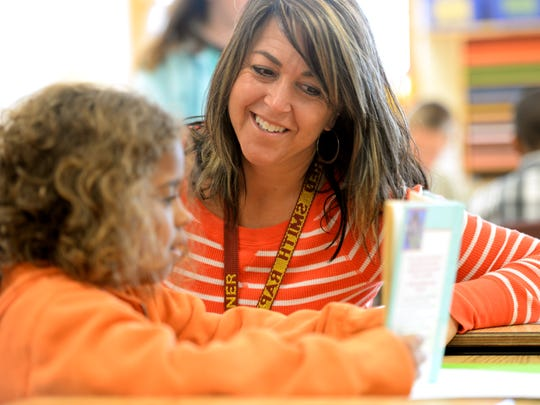 Third grade teacher Tricia Wagner works with Aviana Jean-Baptiste during a reading lesson in her class at Red Smith School September 16, 2014.