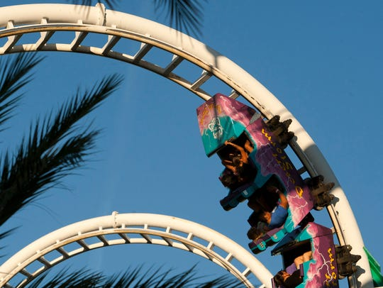 People ride the Desert Storm roller coaster at Castles