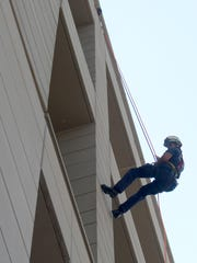 A firefighter slowly climbs down the western face of the Reno Justice Court from the eight floor as part of a rappelling exercise Thursday in downtown Reno. The rappelling practice was part of the first Regional Safety and Emergency Preparedness Expo held in Wingfield Park.