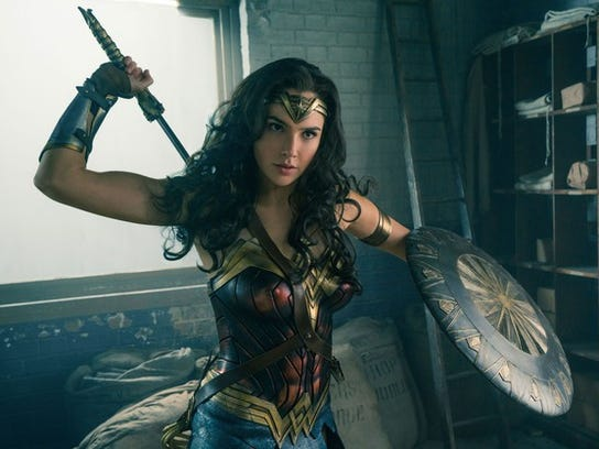 Gal Godot as Wonder Woman holding a shield and sword.