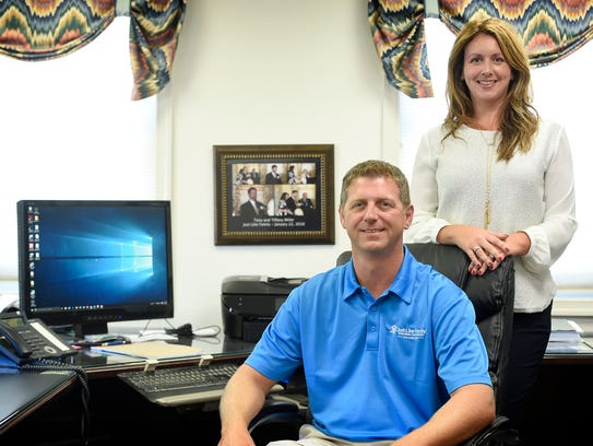 Anthony and Tiffany Miller, pose in the offices of