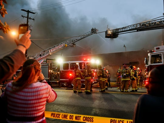 Onlookers watch and use smart phones to record a working fire at a gun range from across West Market Street in West York Friday, Sept. 30, 2016. Emergency personnel responded to a working fire at West York Sporting Goods, a shooting range, in West York.
