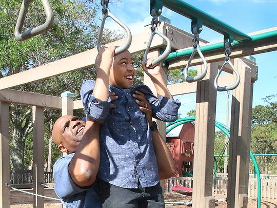 Earl Spann helps his son Davion pull himself up on the rings at the playground.