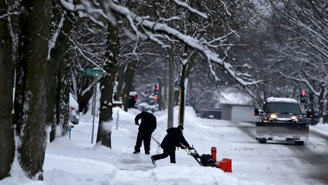 On Telulah Ave., Dave Grimm brings out the shovel while Mike Stremer uses a snowblower as they clear the first significant snowfall of the season Sunday.