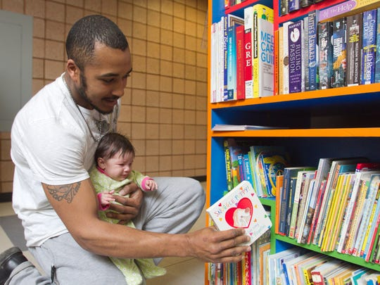"Justin McCallum was the first patron to select a book from the Little Free Library which became available in 2014 to the MiWorks campus at Mott Community College, picking out ""Snuggle Puppy"" to read to his 2-month-old daughtert Tiyana McCallum."