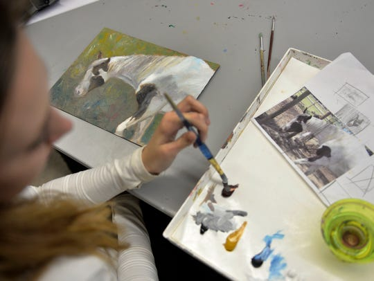 Claire Miller mixes paint as she works on her painting.
