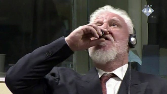 """In this photo provided by the ICTY on Nov. 29, 2017, Slobodan Praljak brings what is believed a bottle to his lips, during a Yugoslav War Crimes Tribunal in The Hague, Netherlands. Praljak yelled, """"I am not a war criminal!"""" and appeared to drink from a small bottle of poison, seconds after judges reconfirmed his 20-year prison sentence for involvement in a campaign to drive Muslims out of a would-be Bosnian Croat ministate in Bosnia in the early 1990s. Praljak was taken to a hospital, where he later died, according to the Croatian state news service HINA."""