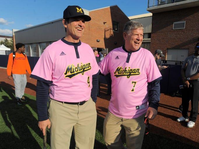 UM football head coach Jim Harbaugh, left, and former