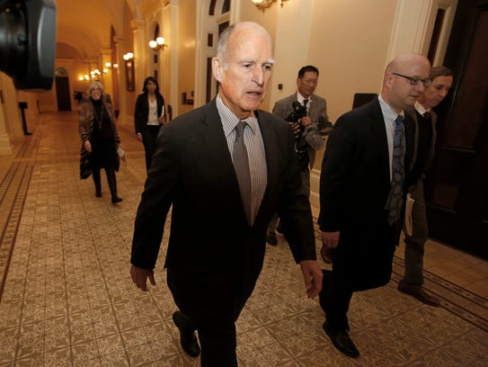 California Gov. Jerry Brown returns to his office after