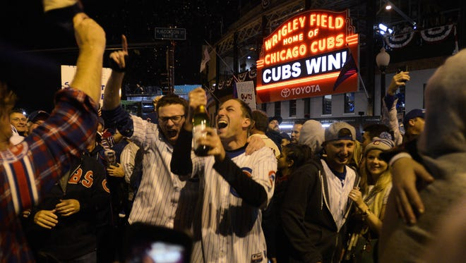Chicago Cubs fans celebrate outside of Wrigley Field after Game 5 of the Major League Baseball World Series against the Cleveland Indians, Sunday, Oct. 30, 2016, in Chicago. The Cubs won 3-2, as the Indians lead the series 3-2. (AP Photo/Matt Marton) ORG XMIT: ILMM119
