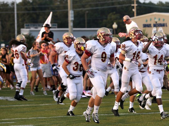 Riverdale players Ben Wells, Gentry Bonds, and Preston Barge take the field with the team before the Siegel vs. Riverdale week zero game at Siegel, on Friday,  August  22, 2014.