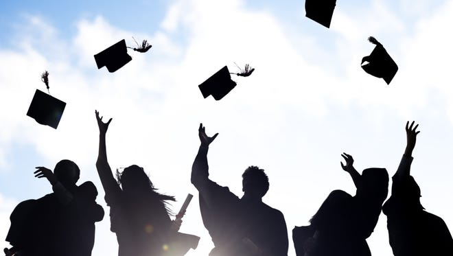 Silhouettes of students celebrating graduation