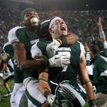 In this Oct. 22, 2011, file photo, Michigan State's Keith Nichol (7), center, and B.J. Cunningham celebrate following a 37-31 win over Wisconsin in an NCAA college football game in East Lansing, Mich.