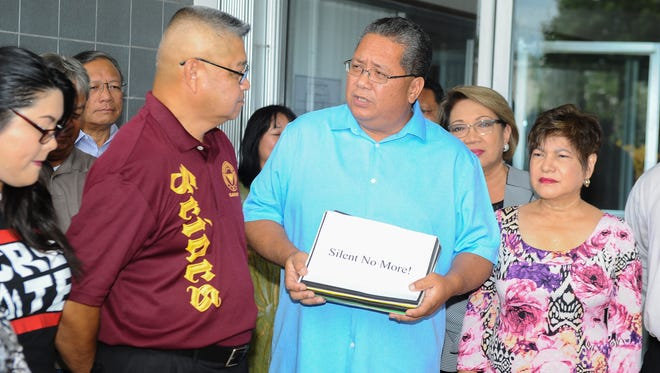In this Sept. 8 file photo, Sen. Frank Blas Jr., center, speaks after receiving a petition with over 3,000 signatures from Silent No More campaign founder Joe Santos, during a brief ceremony at the Guam Legislature in Hagåtña.