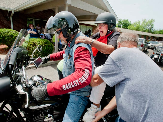 Lucy Thomas, 93, center, who lives at the Wesley Manor Retirement Home gets help from Jerry Hoganson, right, Wesley Manor's CEO and president in mounting a motorcycle  for a ride on a motorcycle. The members of the Derby City Chapter of the Harley (Davidson) Owners Group (HOG) were giving free rides to facility's residents. Driving the vehicle is Paul Andre. 14 June 2014